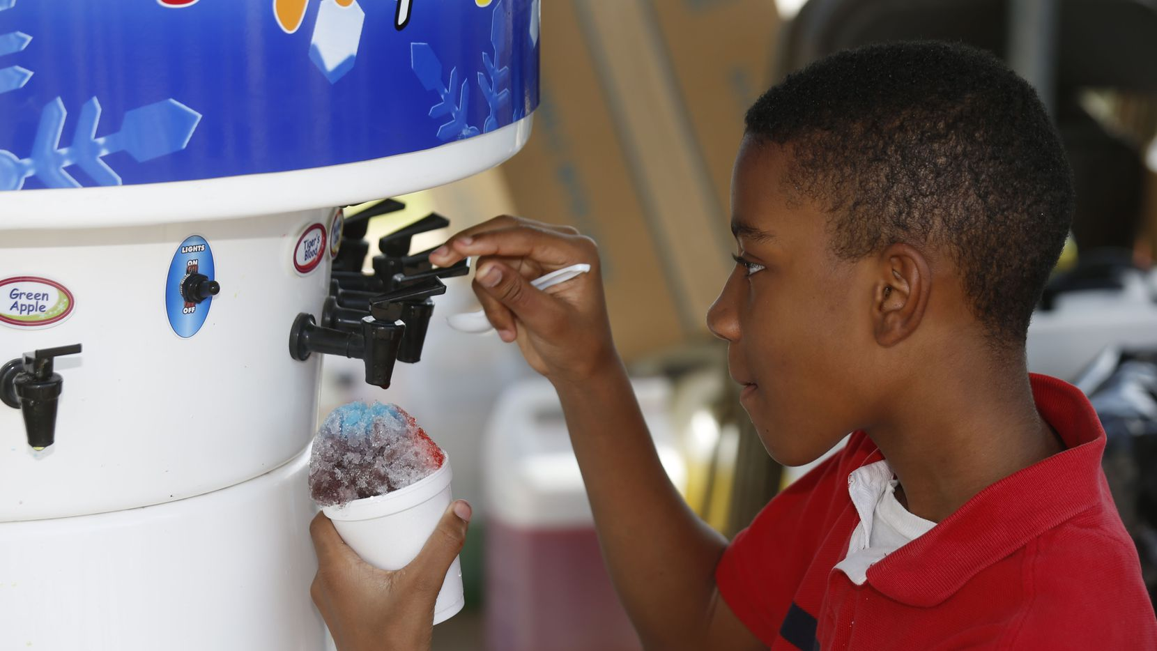 Ashton Smith, 12, makes a custom snow cone at the Snowie Southwest Shaved Ice Snow Cones booth during Taste of Irving at Cimarron Park Recreation Center Saturday May 20, 2017.  The event also offered a fun zone, craft marketplace and live music.