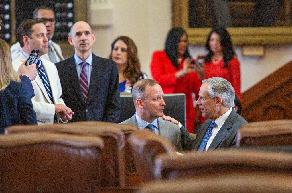 State Rep. Four Price (left), kneels and chats with Gov. Greg Abbott on the House floor just before Sine Die at the State Capitol of Texas on May 27, 2019 in Austin, Texas.