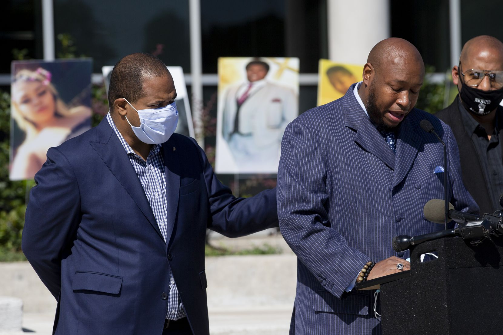 Mayor Eric Johnson (left) consoled Dallas ISD trustee Maxie Johnson as he became emotional speaking about his son's death from gun violence during a news conference about funding for public safety initiatives at South Oak Cliff High School in Dallas in October. Photos of students lost to gun violence were placed outside the school.