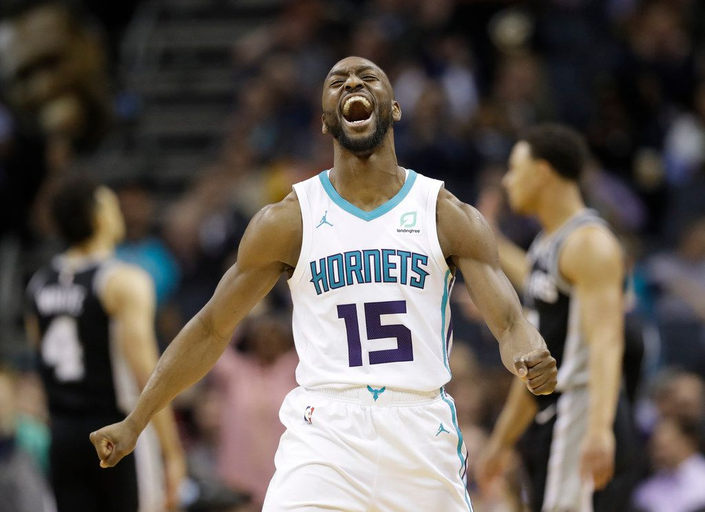 "FILE - In this March 26, 2019, file photo, Charlotte Hornets' Kemba Walker (15) reacts after making a basket against the San Antonio Spurs during the second half of an NBA basketball game in Charlotte, N.C. The three-time All-Star point says he'd be willing to work with the Hornets and take less than the ""supermax"" $221 million contract he's eligible to receive to re-sign with Charlotte (AP Photo/Chuck Burton, File"