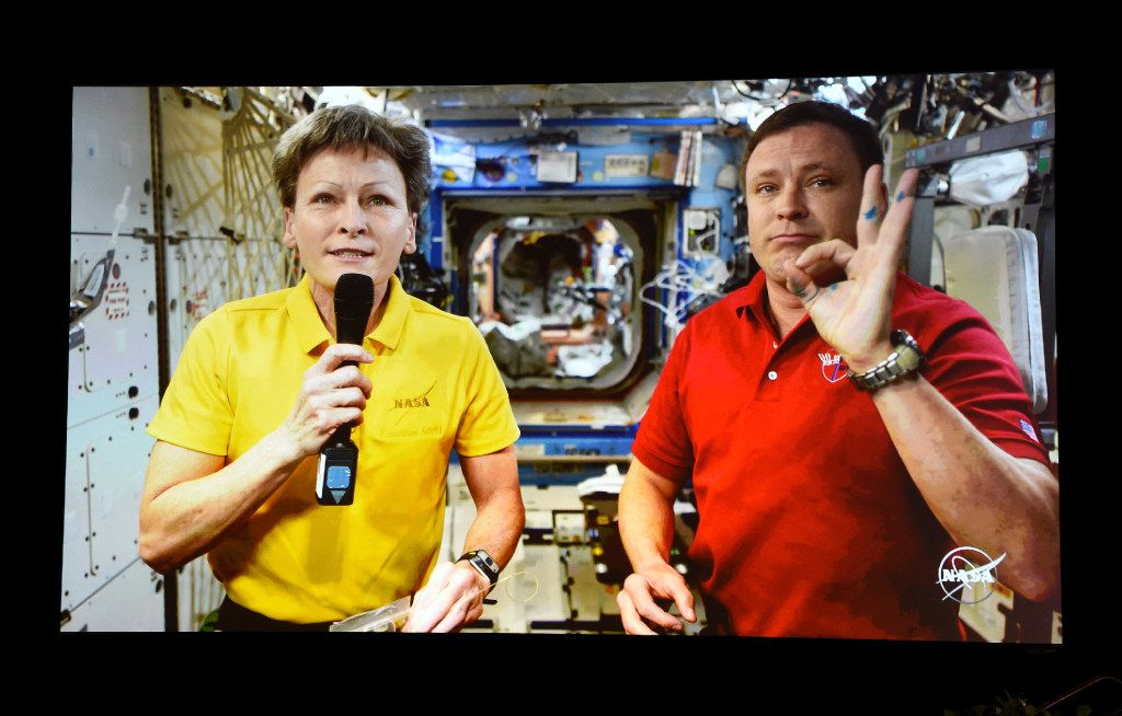"""LAS VEGAS, NV - APRIL 26:  NASA astronauts Cmdr. Peggy A. Whitson (L) and Col. Jack Fischer are shown live on screen from the International Space Station using a RED Epic Dragon camera as part of the first-ever live 4K video stream from space during the panel, """"Reaching for the Stars: Connecting to the Future with NASA and Hollywood"""" at the 2017 NAB Show at the Las Vegas Convention Center on April 26, 2017 in Las Vegas, Nevada. On Monday, Whitson became NASA's astronaut with the most time in orbit with more than 534 days off-planet. NAB Show, the trade show of the National Association of Broadcasters and the world's largest electronic media show, runs through April 27 and features more than 1,700 exhibitors and 103,000 attendees.  (Photo by Ethan Miller/Getty Images)"""