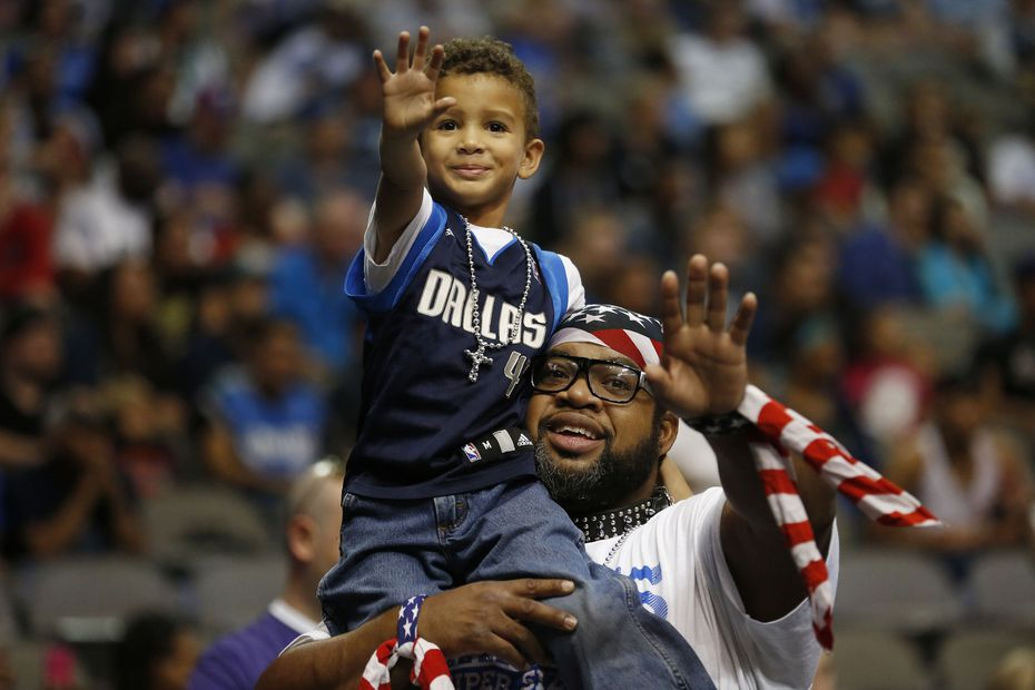 """Mavs ManiAAC Randy Thornton, known as """"Wild Dog,"""" held his son, Jackson Emmanuel Thornton, known as """"Wild Pup,"""" before a scrimmage in 2014 at the Dallas Mavericks Fan Jam at American Airlines Center."""