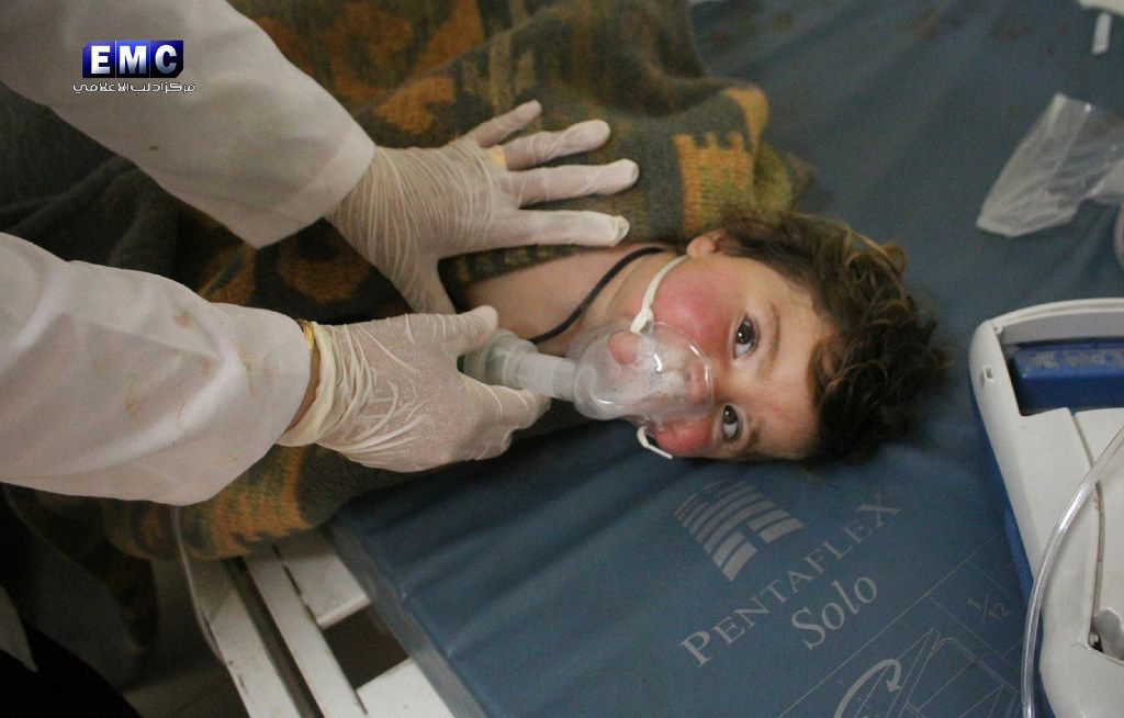 This photo provided Tuesday, April 4, 2017 by the Syrian anti-government activist group Edlib Media Center, which has been authenticated based on its contents and other AP reporting, shows a Syrian doctor treating a child following a suspected chemical attack, at a makeshift hospital, in the town of Khan Sheikhoun, northern Idlib province, Syria. The suspected chemical attack killed dozens of people on Tuesday, Syrian opposition activists said, describing the attack as among the worst in the country's six-year civil war. (Edlib Media Center, via AP)