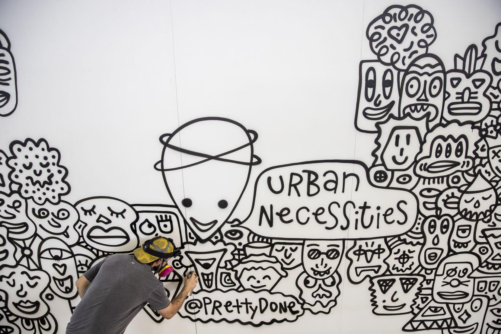 Las Vegas-based artist Adam Rellah, known as Pretty Done, spray paints a mural in preparation for Sneaker Con.