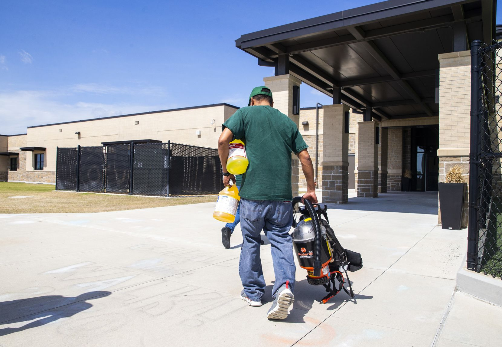 Custodian George Cox (right) carries a respirator and cleaning supplies into Jim Spradley Elementary School in Frisco, Texas, on Thursday, March 12, 2020. Frisco ISD custodial crews worked to disinfect campuses throughout Thursday in light of the COVID-19 global pandemic.