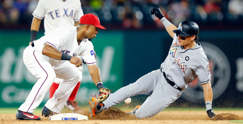Miami Marlins Derek Dietrich slides safely into second on his two-RBI double in the eighth inning. Texas Rangers shortstop Elvis Andrus (1) couldn't handle the thrown in from right center field at Globe Life Park in Arlington, Wednesday, July 26, 2017. (Tom Fox/The Dallas Morning News)