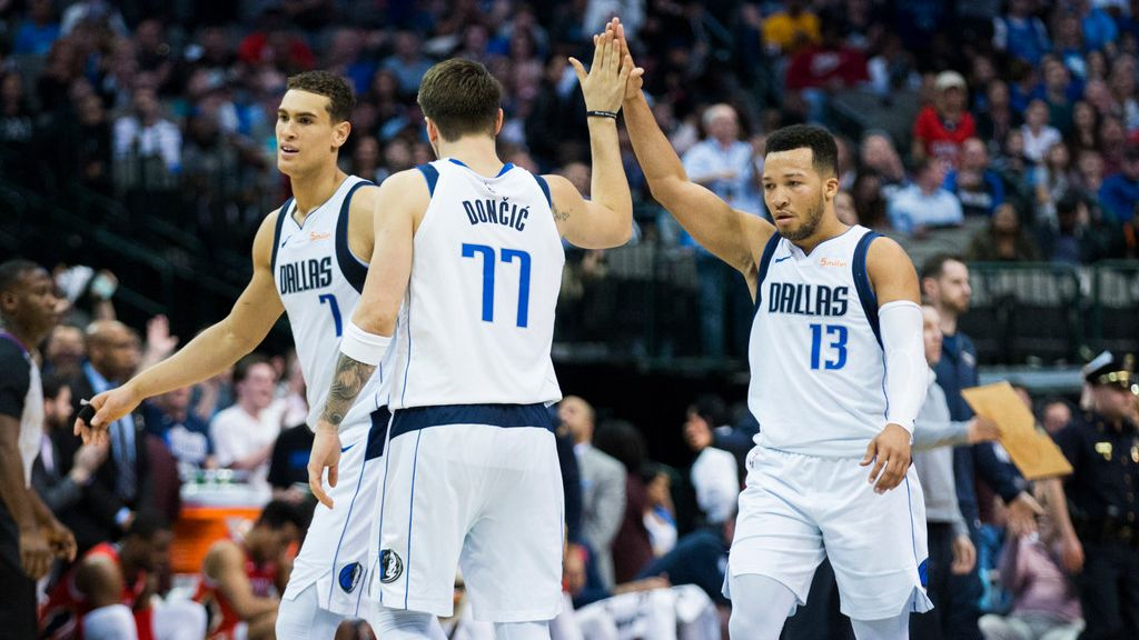 Mavericks guards Luka Doncic (77) and Jalen Brunson (13) and forward Dwight Powell (7) celebrate at a timeout during the fourth quarter of a game against the Pelicans on Monday, March 18, 2019, at American Airlines Center in Dallas.