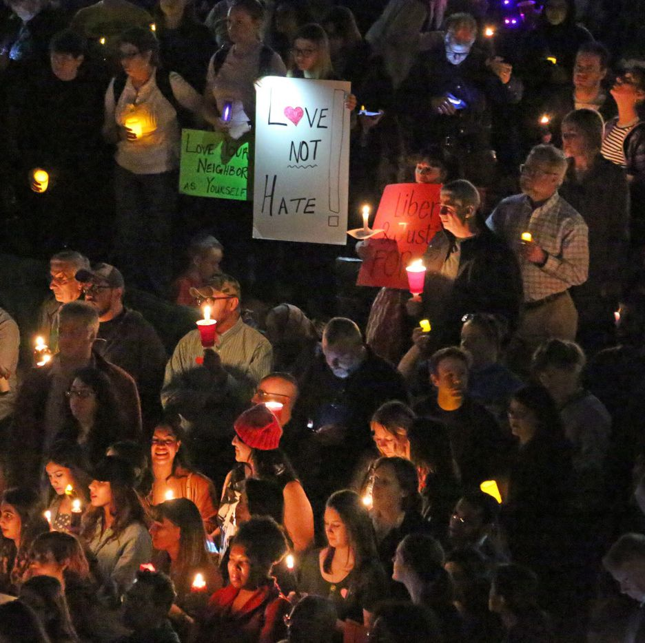 The crowd holds candles during the interfaith vigil to support refugee resettlement in Texas and denounce the Trump administration's executive action on refugee resettlement. photographed at Thanksgiving Square in Dallas on Monday, January 30, 2017.