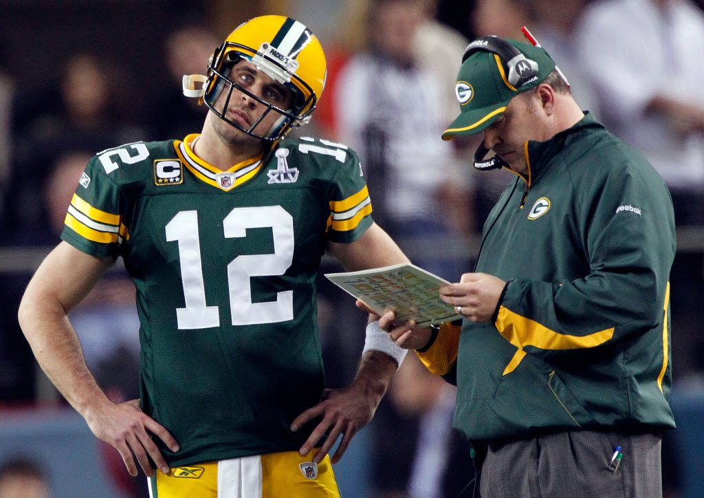 FILE — Green Bay Packers quarterback Aaron Rodgers listens to head coach Mike McCarthy in Super Bowl XLV, February 6, 2011.