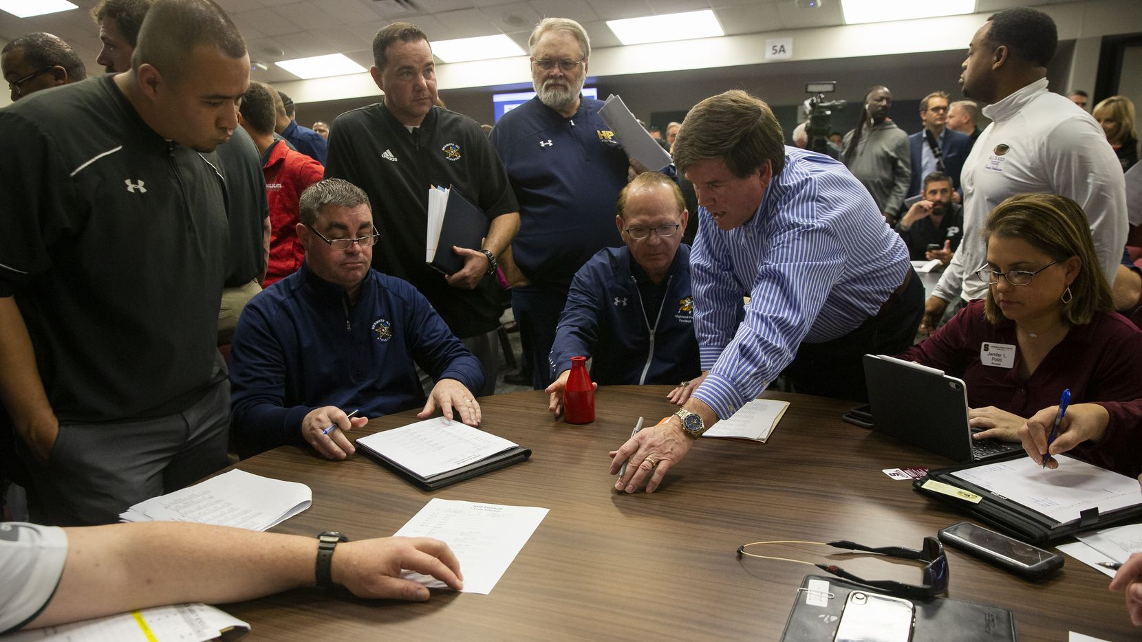 The Mesquite coaching staff, the Highland Park staff (including Highland Park head football coach Randy Allen (center, seated) and other area schools work on scheduling games following the UIL realignment announcement at the Birdville Fine Arts/Athletics Complex on Feb. 3, 2020 in North Richland Hills.