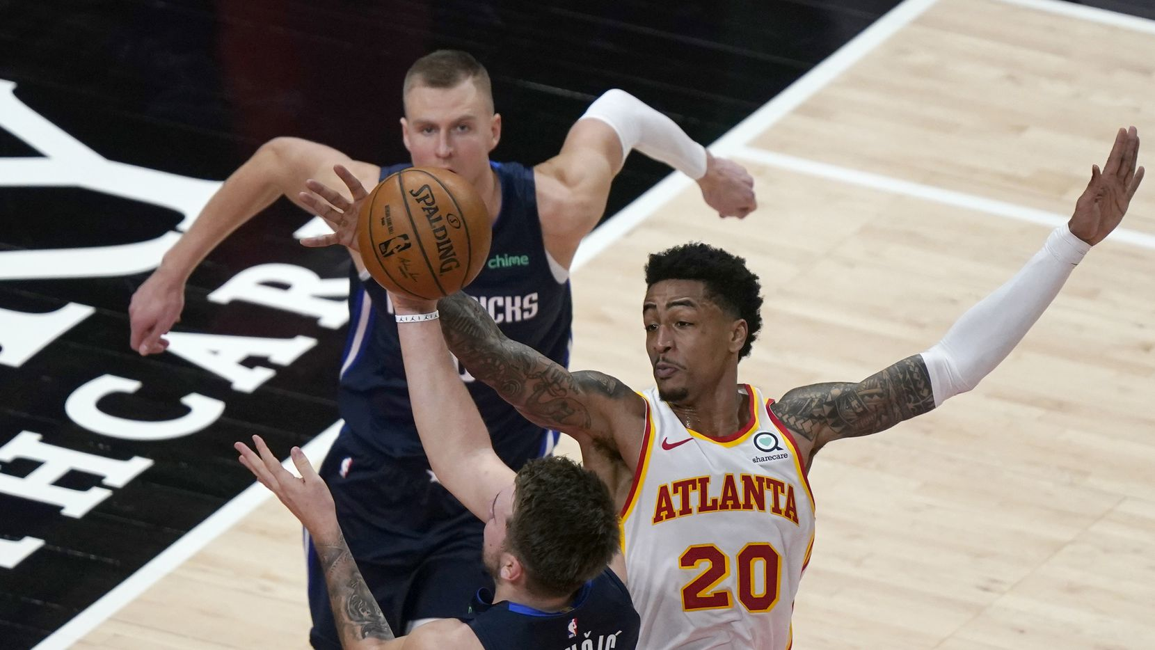 Dallas Mavericks guard Luka Doncic (77) is defended by Atlanta Hawks forward John Collins (20) during the second half of an NBA basketball game Wednesday, Feb. 3, 2021, in Atlanta. Mavericks forward Kristaps Porzingis is at rear. (AP Photo/John Bazemore)