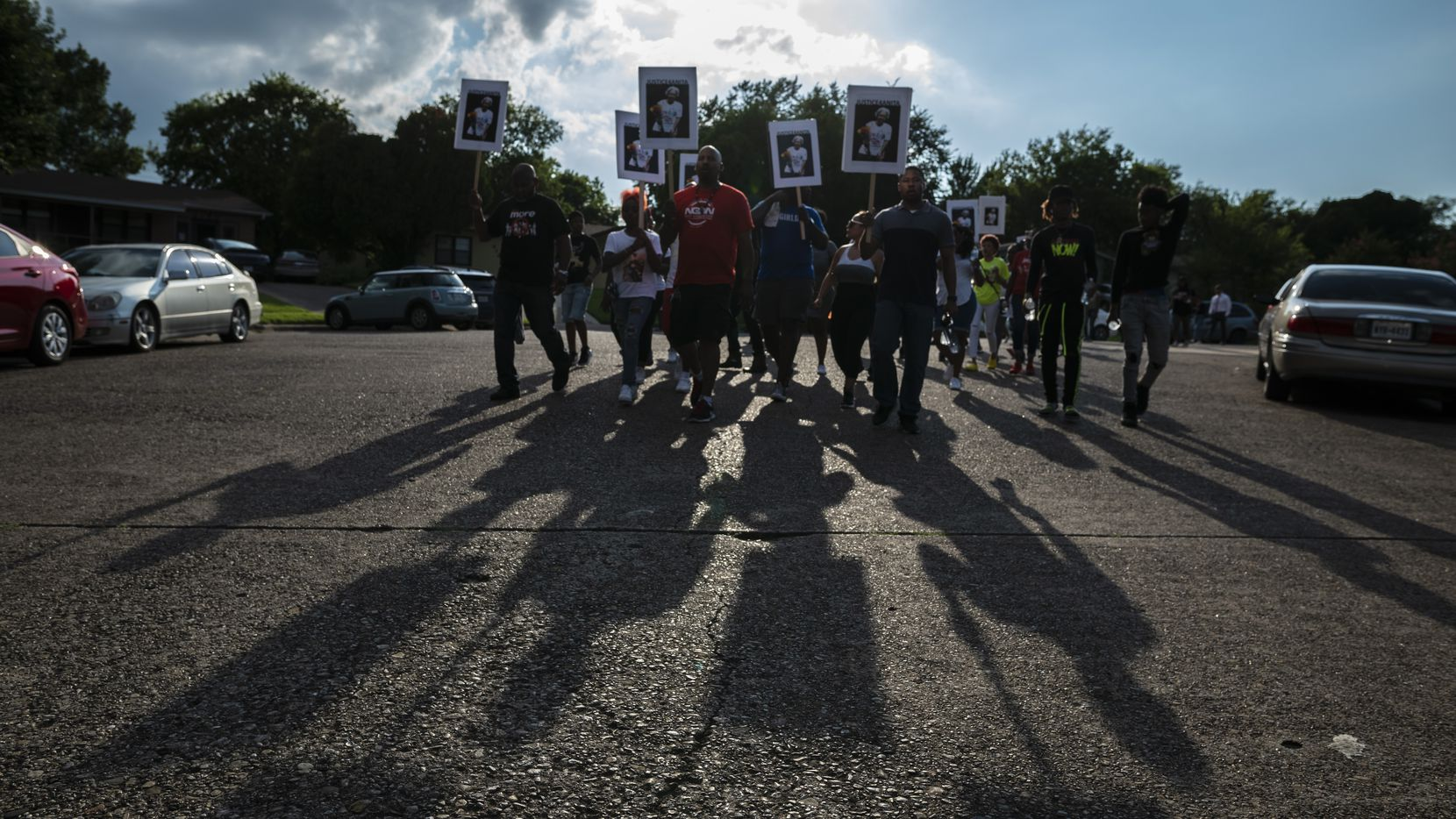 Friends and family march from Anita Thompson's home on Fortune Lane to the Glendale Shopping Center carrying signs with an image of Thompson after the group conducted a prayer vigil outside her home in east Oak Cliff.