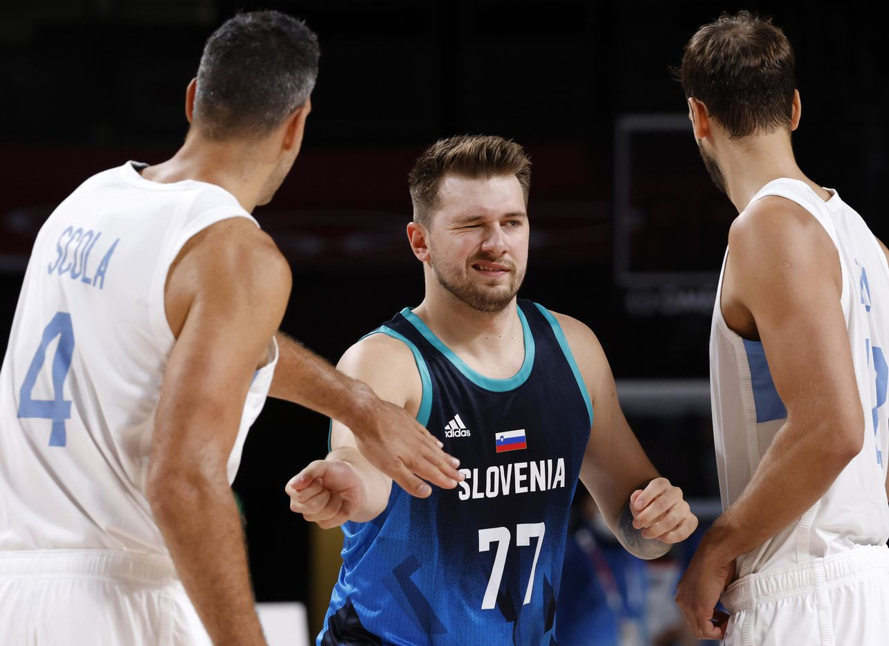 Slovenia's Luka Doncic (77) winks as he slaps hands with Argentina's Luis Scola (4) before tipoff during the postponed 2020 Tokyo Olympics at Saitama Super Arena on Monday, July 26, 2021, in Saitama, Japan. Slovenia defeated Argentina 118-100. (Vernon Bryant/The Dallas Morning News)