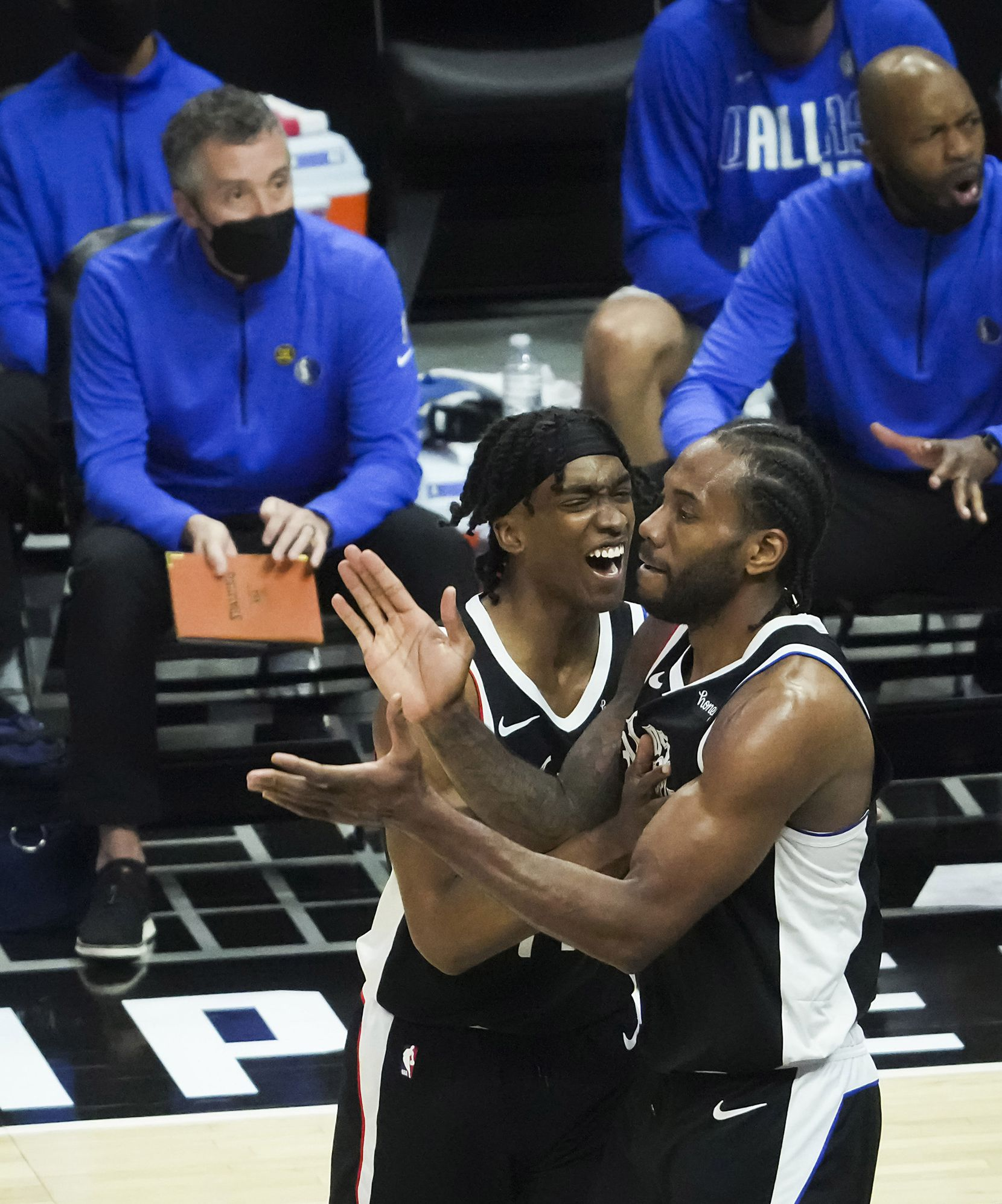 LA Clippers forward Kawhi Leonard (2) celebrates with guard Terance Mann (14) after a basket during the fourth quarter of Game 7 of an NBA playoff series against the Dallas Mavericks at the Staples Center on Sunday, June 6, 2021, in Los Angeles.