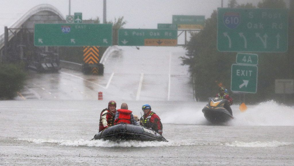Meyerland resident Connor Childs, in orange life jacket, and his dog Lacey are rescued by officials from their home by transporting them by boat along Interstate 610 south during heavy rains from Hurricane Harvey in Houston on Sunday, August 27, 2017. (Louis DeLuca/The Dallas Morning News)