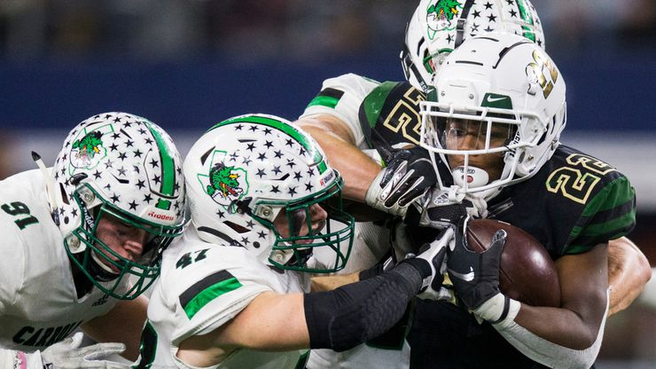 DeSoto running back  Jyison Brown (22) is tackled by Southlake Carroll defenders during the third quarter of a Class 6A Division I area-round high school football playoff game between Southlake Carroll and DeSoto on Friday, November 22, 2019 at AT&T Stadium in Arlington.