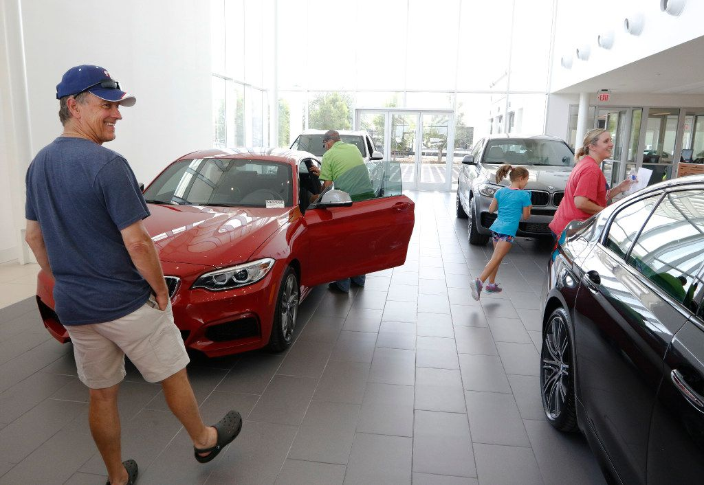 David Renken, from left, Dale Allen, Ella Renken, 8, and Michele Renken, excited while shopping for a new BMW at Sewell BMW of Grapevine on Friday, July 3, 2017. Sewell BMW of Grapevine has 300,000 square feet in their new location and is the largest BMW dealership in Texas and among the largest in the world. The dealership features a two-story showroom showcasing 35 of the latest BMW models. Photo taken on Friday, July 3, 2017. (David Woo/The Dallas Morning News)