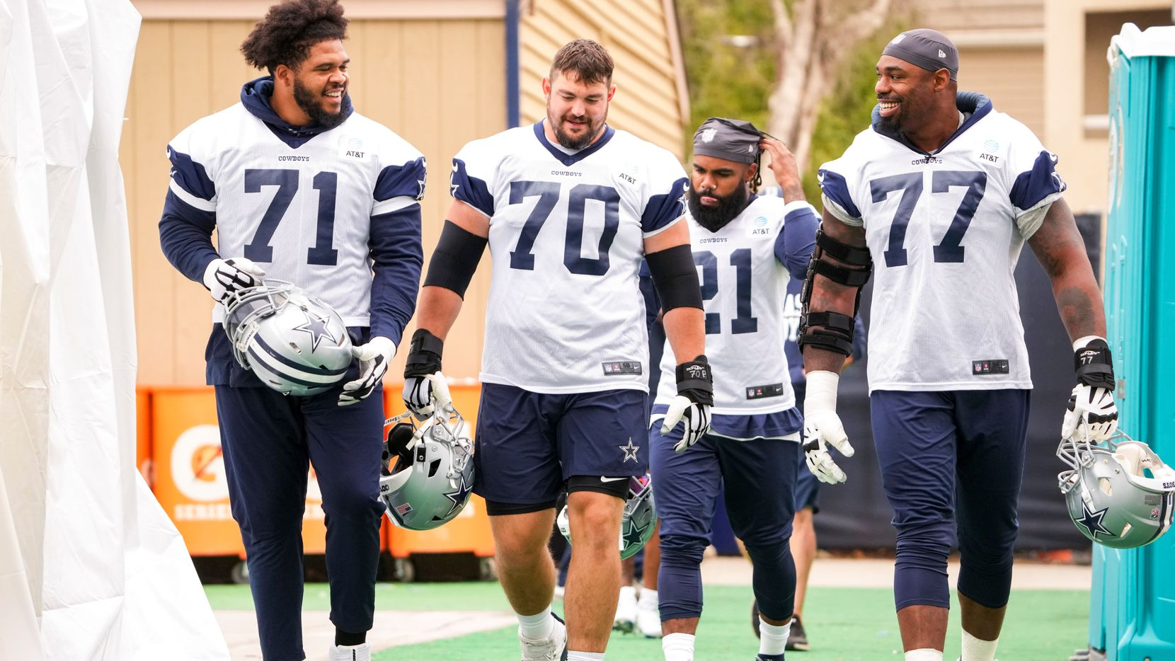 Dallas Cowboys tackle La'el Collins (71), guard Zack Martin (70), running back Ezekiel Elliott (21) and tackle Tyron Smith (77) take the field for a practice at training camp on Saturday, July 24, 2021, in Oxnard, Calif.