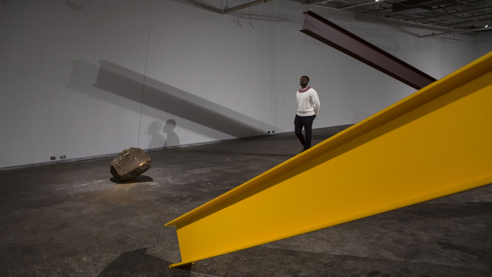 """Visitor Olajide Asekun checks out artist Jose Davila's """"Directional Energies"""" during a past exhibition at the Dallas Contemporary. The venue announced Monday that it will stay closed for the rest of 2020."""