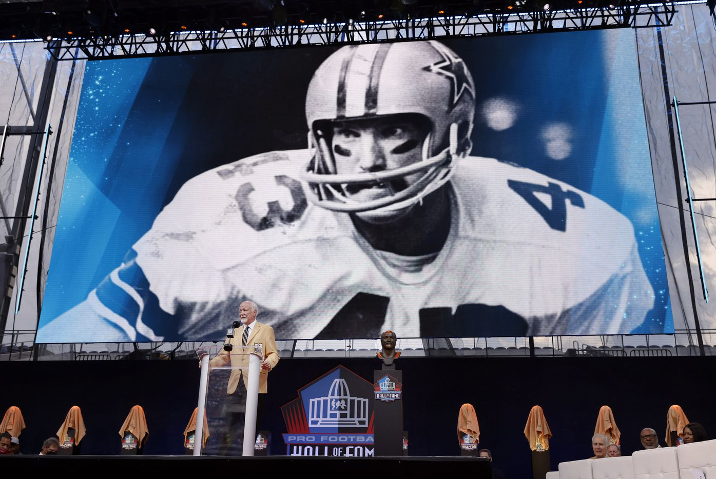 Before a large photo from his playing days, Pro Football Hall of Fame inductee Cliff Harris of the Dallas Cowboys delivers his speech during the Centennial Class of 2020 enshrinement  ceremony at Tom Benson Hall of Fame Stadium in Canton, Ohio, Saturday, August 7, 2021. (Tom Fox/The Dallas Morning News)