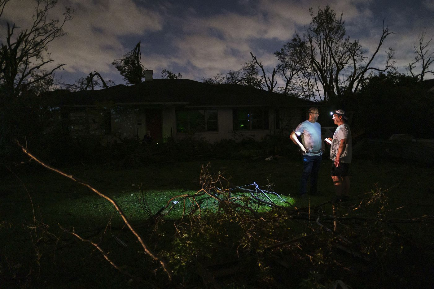 Residents survey tornado damage to their darkened neighborhood near the intersection of Royal and Hillcrest on Sunday, Oct. 20, 2019, in Dallas.