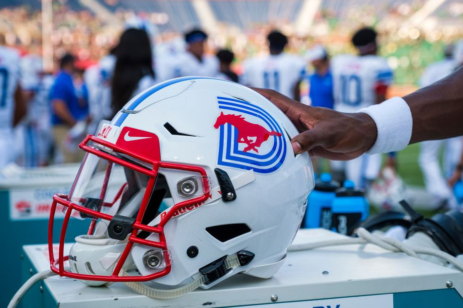 A SMU player grabs his helmet before an NCAA football game against UNT at Ford Stadium on Saturday, Sept. 7, 2019, in Dallas.