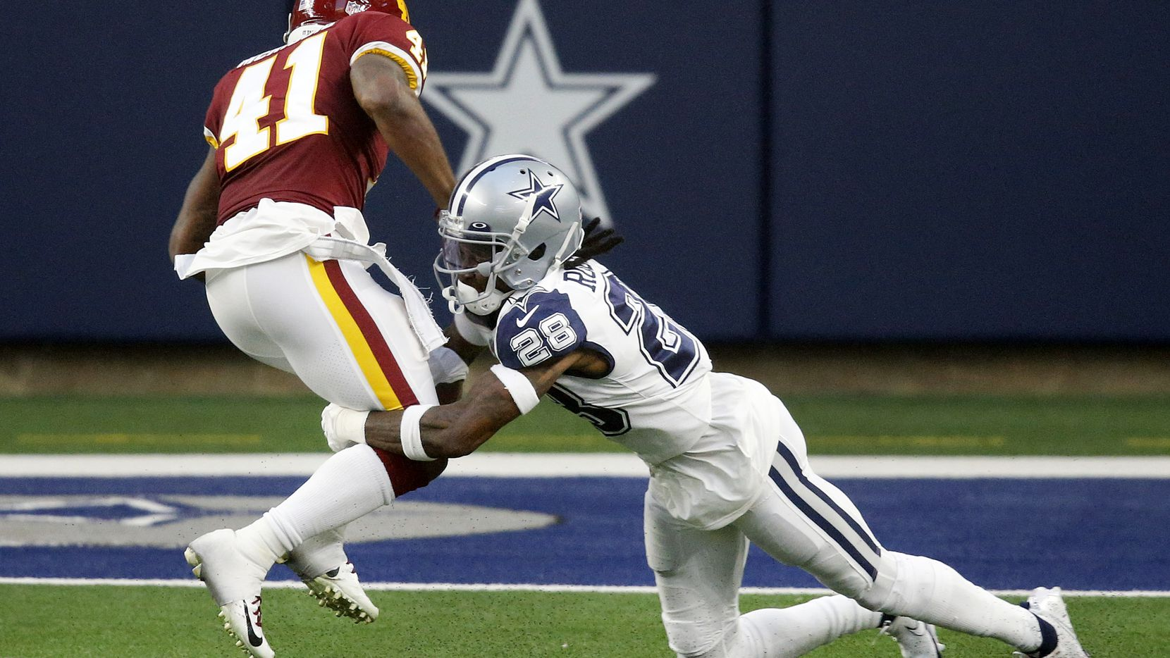 Dallas Cowboys defensive back Rashard Robinson (28) attempts to tackle Washington Football Team defensive back Dee Delaney (41) during the second quarter at AT&T Stadium in Arlington, Thursday, November 26, 2020.