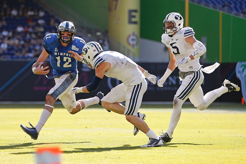 MIAMI, FL - DECEMBER 22: Paxton Lynch #12 of the Memphis Tigers carries as Skye PoVey #7 and Alani Fua #5 of the Brigham Young Cougars defend during the first half of the game at Marlins Park on December 22, 2014 in Miami, Florida.  (Photo by Rob Foldy/Getty Images)