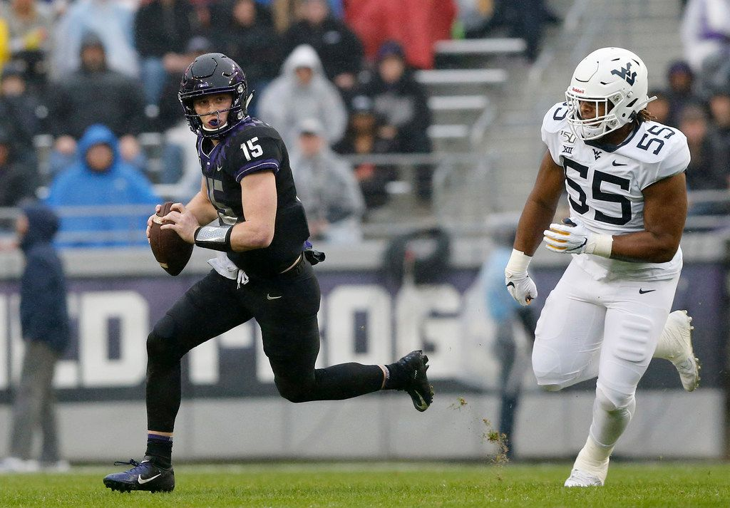 TCU Horned Frogs quarterback Max Duggan (15) races away form West Virginia Mountaineers defensive lineman Dante Stills (55) during the first quarter at Amon G. Carter Stadium in Fort Worth, Friday, November 29, 2019.