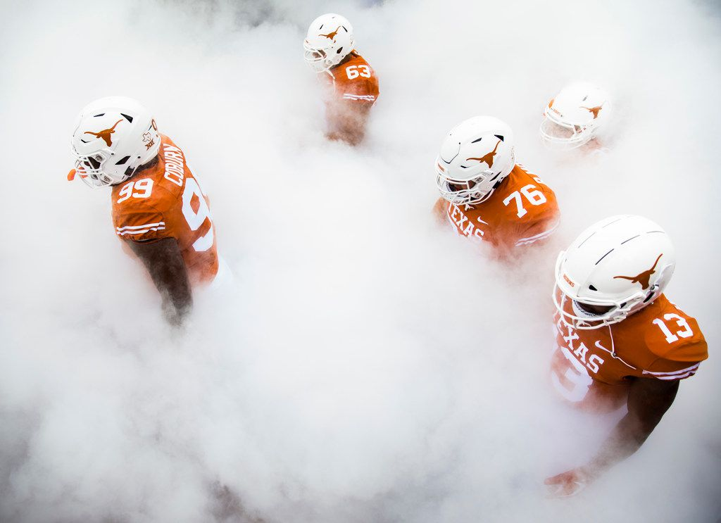 Texas Longhorns walk through smoke to enter the stadium before a college football game between TCU and the University of Texas on Saturday, September 22, 2018 at Darrell K Royal - Texas Memorial Stadium in Austin. (Ashley Landis/The Dallas Morning News)