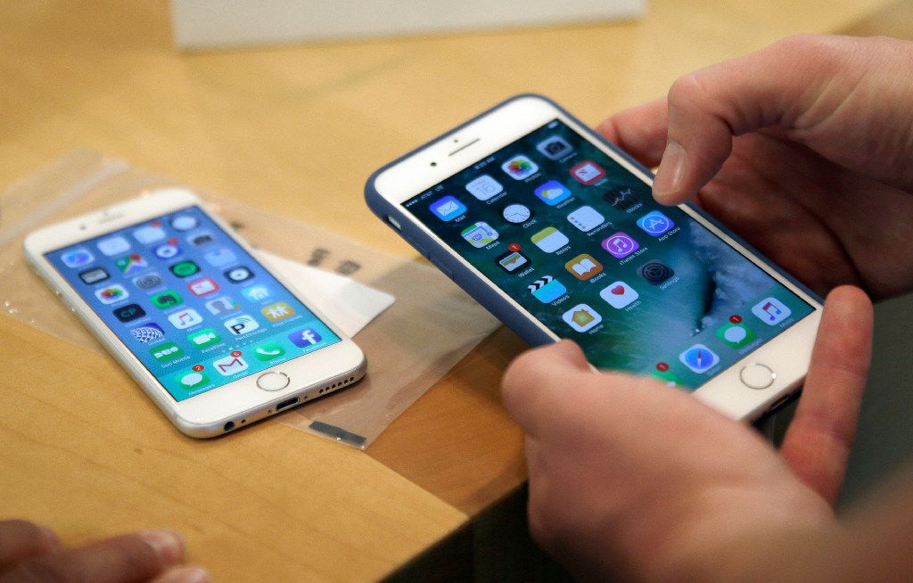FILE - In this Friday, Sept. 16, 2016, file photo, a customer sets up his new iPhone 7 Plus, right, as he switches from the iPhone 6 at the Apple Store on Michigan Avenue during the release of the Apple iPhone 7 and the latest Apple Watches, in Chicago. New documents from WikiLeaks, posted Thursday, March 23, 2017, point to an apparent CIA program to hack Apple's iPhones and Mac computers such that the exploits persist even after the devices are reset to factory conditions. Apple says the purported hacking techniques have all been fixed in recent iPhones and Mac computers. (AP Photo/Kiichiro Sato, File)
