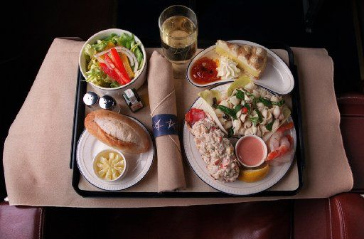 Legend Airlines served this dinner on flights outbound from Dallas Love Field. Lower right: Lobster tail meat mixed with mango, red bell pepper, dill and spices; a fresh spinach-and-black-olive pasta salad in a creamy herb dressing; and shrimp cocktail with a French cocktail sauce.  Lower left: rustic sourdough roll with butter. Upper left: Salad of green leaf lettuce with red onion and balsamic dressing. Upper right: lemon cheesecake. Beverage: Domaine St. Vincent Brut champagne.