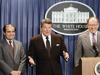 In this June 17, 1986, file photo, President Ronald Reagan announces thenomination of Antonin Scalia, left, to the Supreme Court as a result of Chief Justice Warren E. Burger's resignation. William Rehnquist is at right. Scalia died on Saturday. (AP Photo/Ron Edmonds)