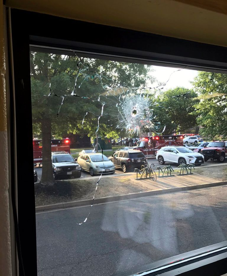 Emergency personnel are seen through a window with a bullet hole in Alexandria, Va., Wednesday, June 14, 2017. House Majority Whip Steve Scalise of Louisiana and others were shot Wednesday at a congressional baseball practice, officials said.