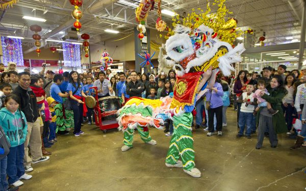 A crowd of shoppers at Asia Times Square watches the lion dance.