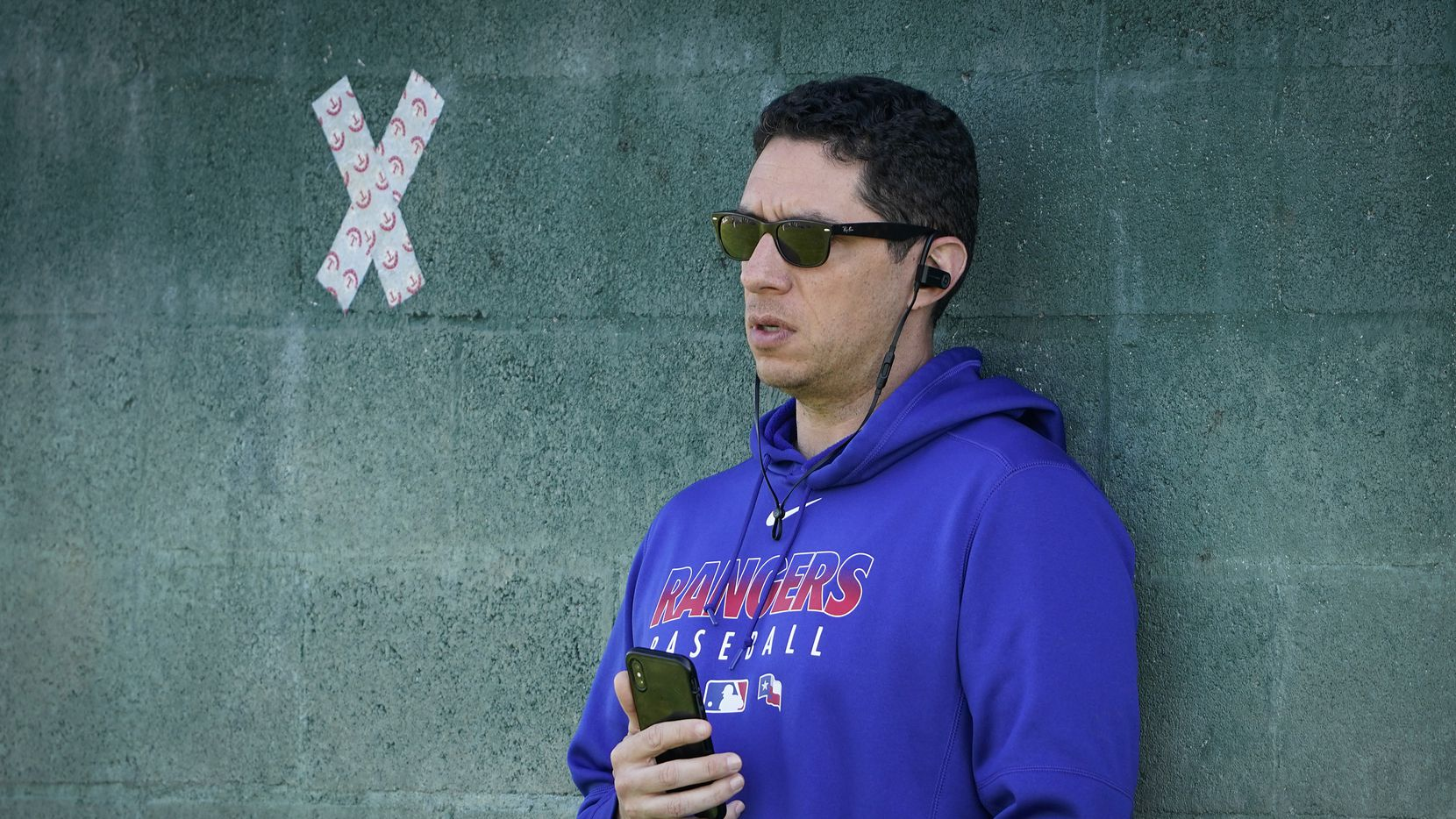Texas Rangers general manager Jon Daniels leans against a wall in the bullpen while talking on the telephone during a spring training workout at the team's training facility on Sunday, Feb. 16, 2020, in Surprise, Ariz.