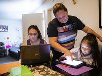 Hebreny Cojulum, de 19 años, toma una de sus clases mientras su madre Adali Arriaza ayuda a su hermana Daysha Cojulum, de 5 años. La opción virtual en el DISD fue problemática debido a que muchos estudiantes no tenían buena conectividad de internet.