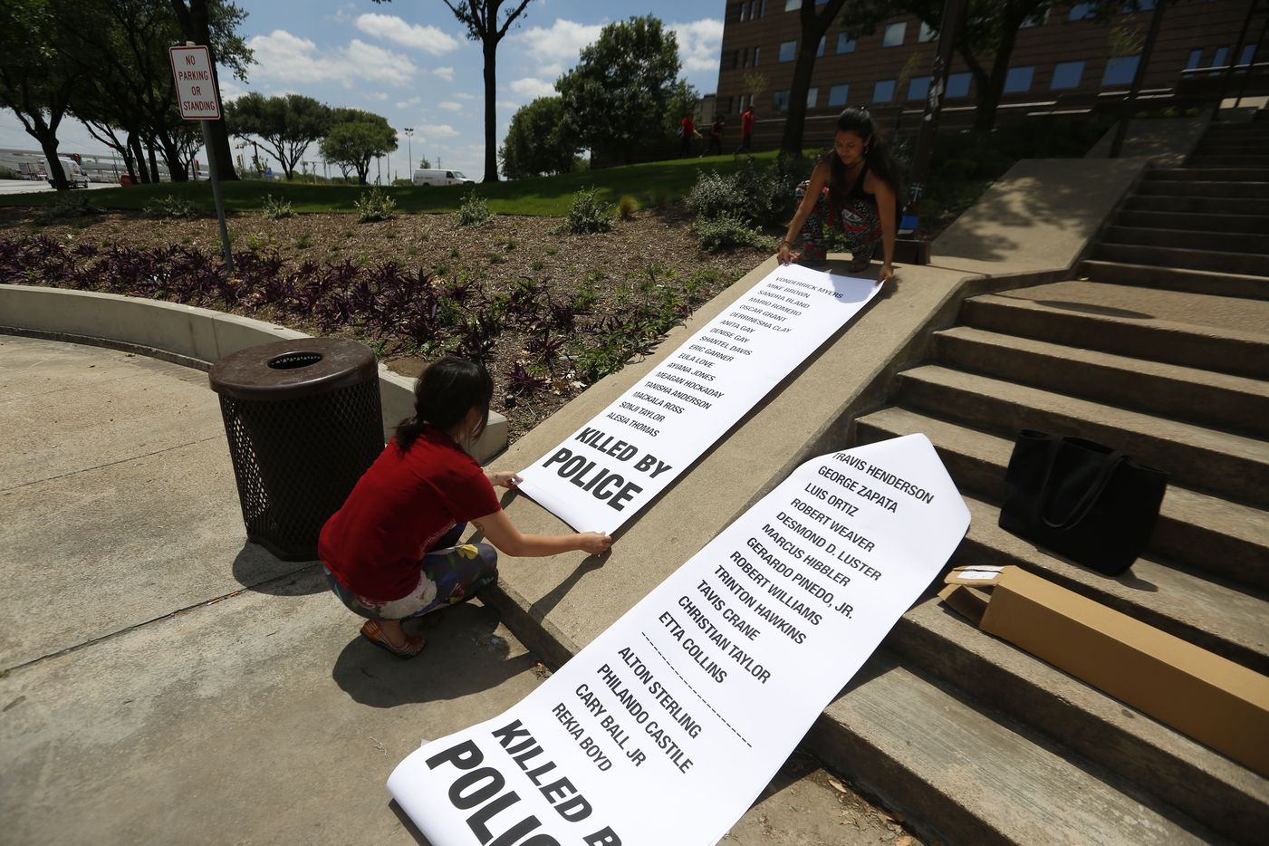 Carol Zoila, left, and Edyka Chiliomé  place banners of names of people killed by police on the steps of the Frank Crowley Courts Building.