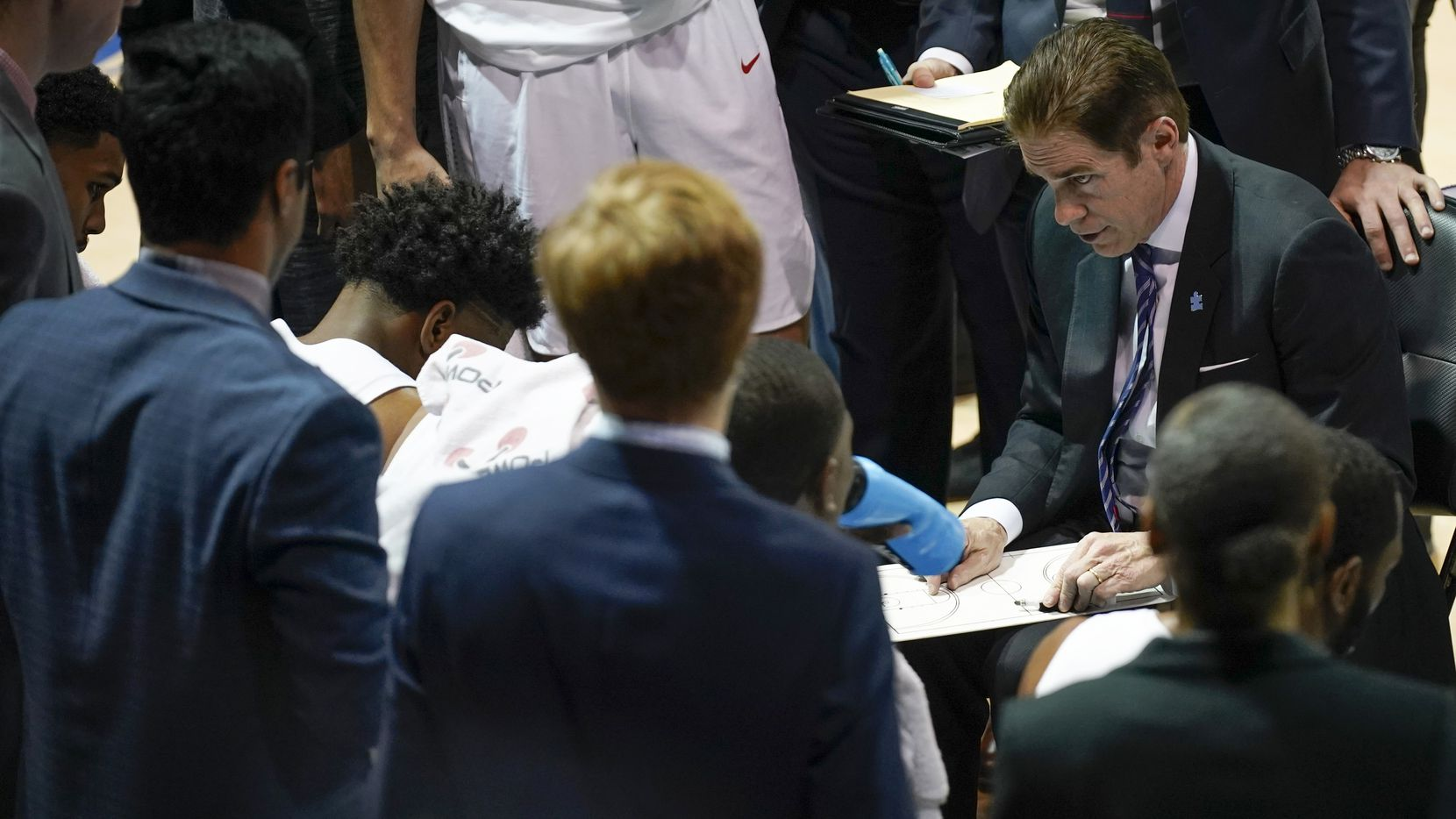 SMU players huddles around head coach Tim Jankovich during a time out in the first half of an NCAA basketball game against Tulane at Moody Coliseum on Saturday, Feb. 1, 2020, in Dallas.