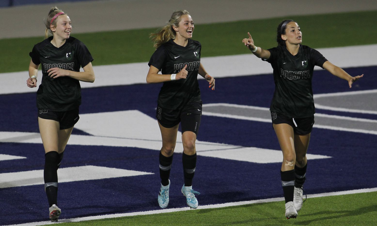 Framed by teammates Hadley Murrell (10), left, and Emma Yolinsky (11), right, Prosper forward Kaitlyn Giametta (3), center, is all smiles as the trio celebrated her goal against Coppell during first half action. The two teams played their Class 6A bi-district girls soccer playoff game at McKinney ISD Stadium in McKinney on March 26, 2021.