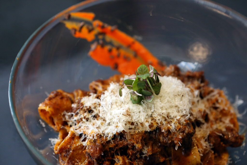Smoked carrot pappardelle with chicken mole sausage and cocoa nibs in a light lemon sauce is garnished with grated Manchego.