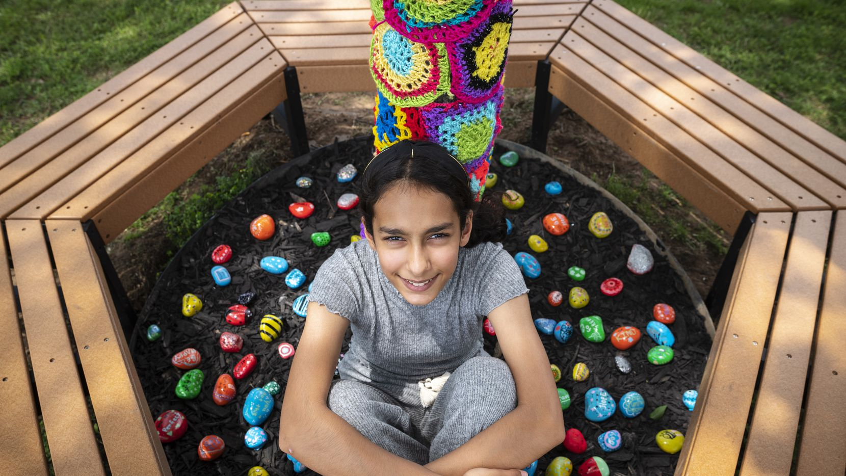 Anya Ali, 12, spearheaded a project to decorate a tree trunk with crochet for a new reading area at the Bedford Public Library. The project includes a sitting area and painted-rock decorations.