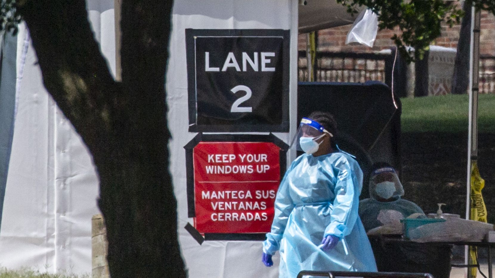 Medical personnel wait for visitors to arrive at the drive-thru COVID-19 testing site located at the University of Dallas campus in Dallas on Friday, July 9, 2020.