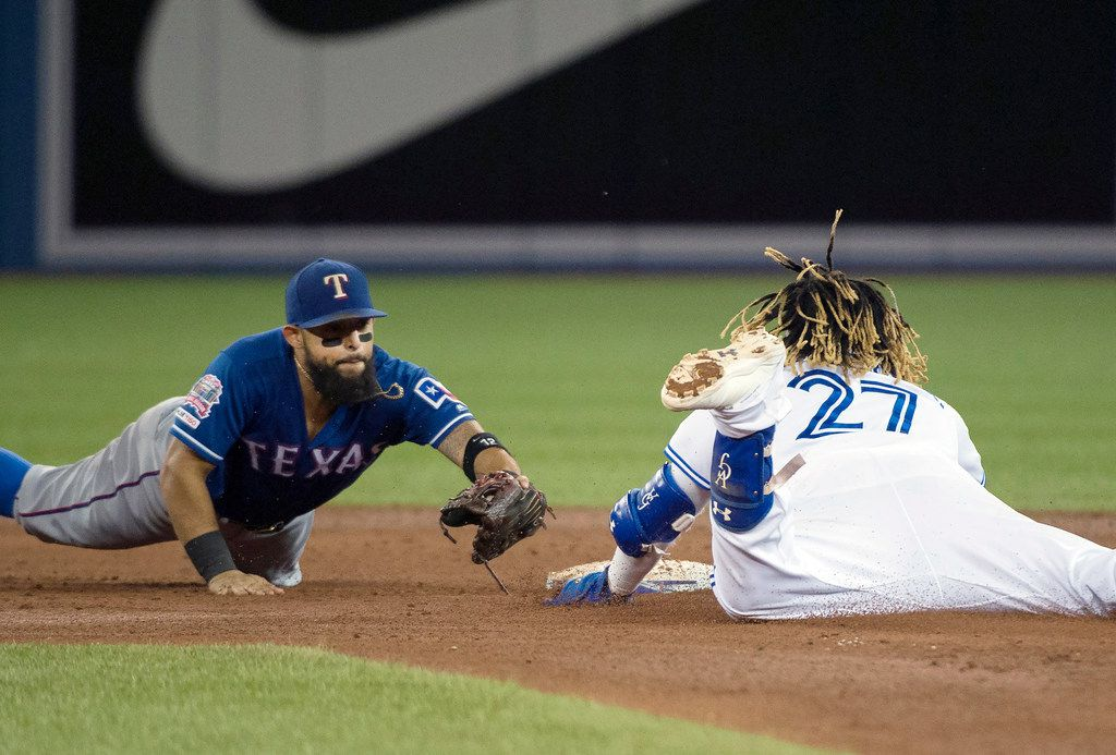 Toronto Blue Jays third baseman Vladimir Guerrero Jr. (27) slides safe past Texas Rangers second baseman Rougned Odor (12) after hitting a double during the fifth inning of a baseball game, Tuesday Aug. 13, 2019 in Toronto. (Nathan Denette/The Canadian Press via AP)