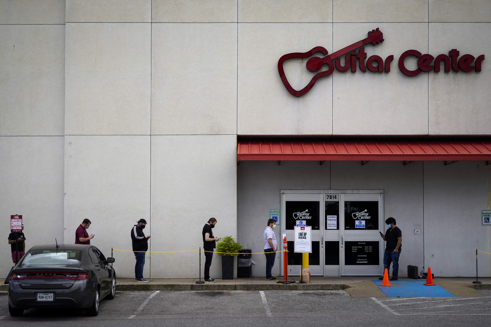 Customers kept social distancing as they waited to enter the Guitar Center store at 7814 N. Central Expressway on May 8, 2020, in Dallas. With retailers able to open at 25% occupancy, customers are only allowed to enter after another exits.
