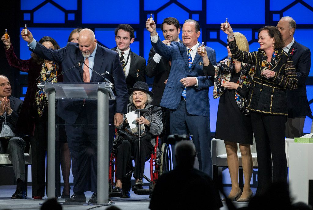 Family members, including wife Joan Kelleher, seated at center, of the late Southwest Airlines co-founder Herb Kelleher raise bottles of Wild Turkey in tribute on Tuesday.