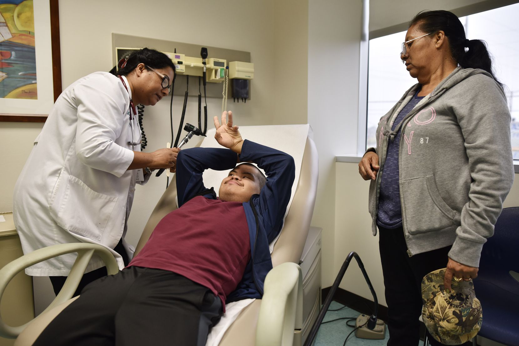 Nurse practitioner Jhudy Mohan examined a shy Roberto Martinez, 21, as his mother Maria Martinez looked on during at Los Barrios Unidos Community Clinic in Dallas last year.