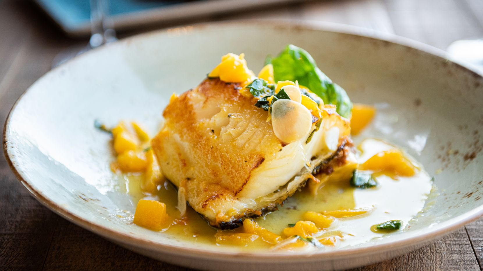 Pan seared sea bass with Italian black truffle potato-fennel gratin and yellow tomato basil sauce. The dish is part of Cru Food and Wine Bar's 2019 four-course New Year's Eve menu.