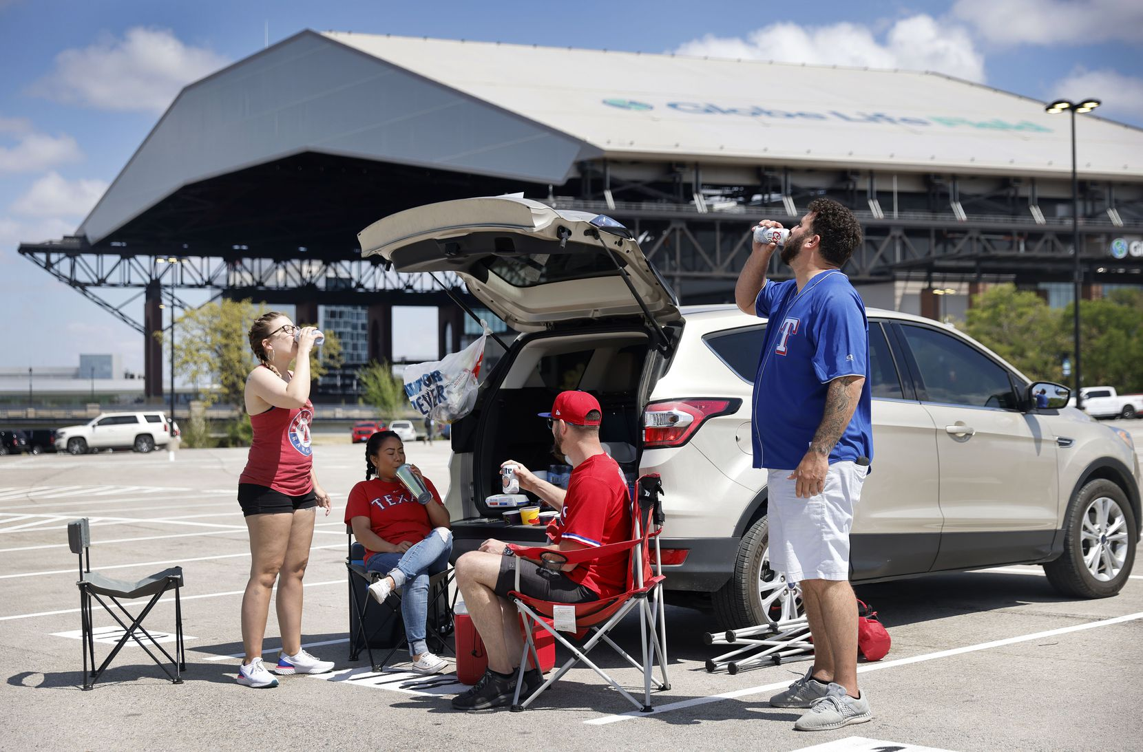 Texas Rangers fans (from left) Tiffany Phillips, Scout Chitavong, Jaime Shannon, and Cameron Johnson of Fort Worth enjoy an Opening Day tailgate party outside of Globe Life Field in Arlington, Monday, April 5, 2021. The Rangers are facing the Toronto Blue Jays in the home opener. (Tom Fox/The Dallas Morning News)