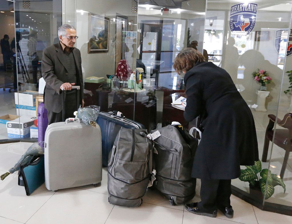 Detainees Mahmood Ghotbi Ravandi and Eshrat Soheili of Iran collect their luggage after a media briefing in North Dallas on Sunday, January 29, 2017.